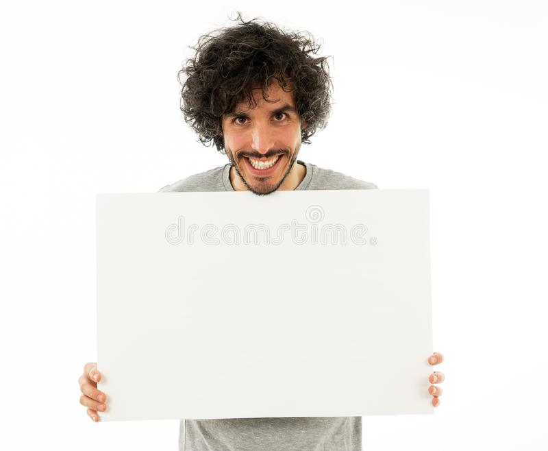 Young funny man holding blank board for advertisement. Millennial men pointing at white billboard royalty free stock photography