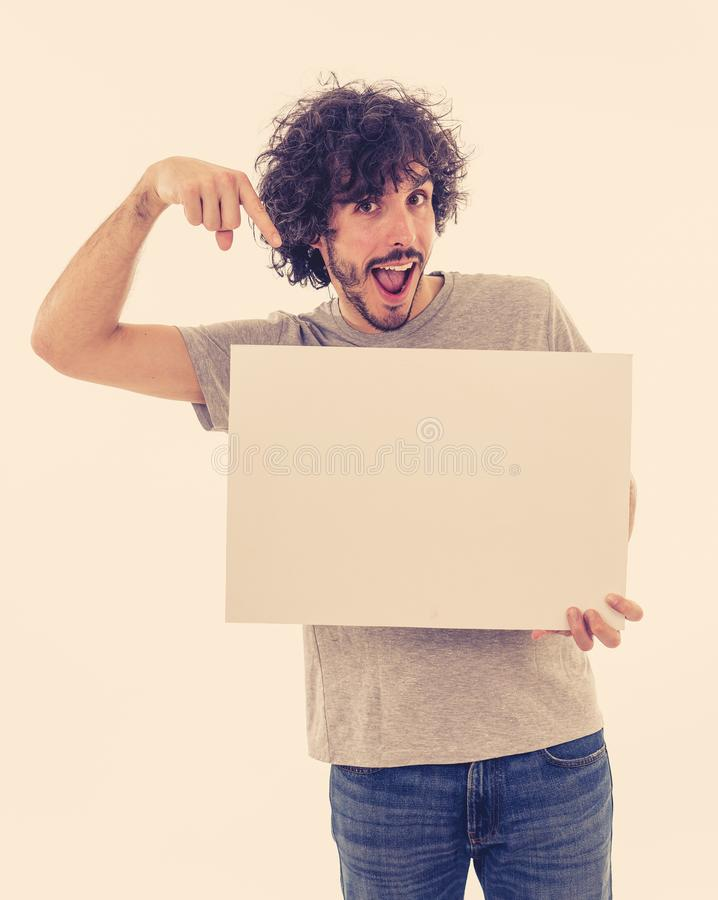 Young funny man holding blank board for advertisement. Millennial men pointing at white billboard stock images