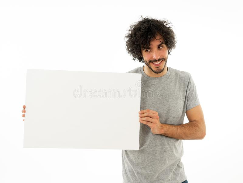 Young funny man holding blank board for advertisement. Millennial men pointing at white billboard stock photo