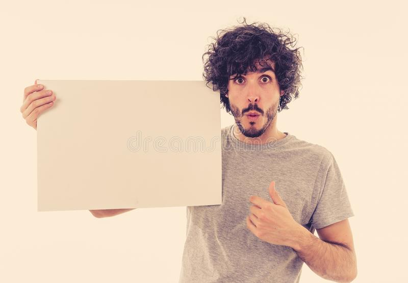 Young funny man holding blank board with happy and surprised face showing and selling product stock photography