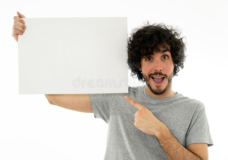Young funny man holding blank board looking surprised and happy pointing at the add royalty free stock photos