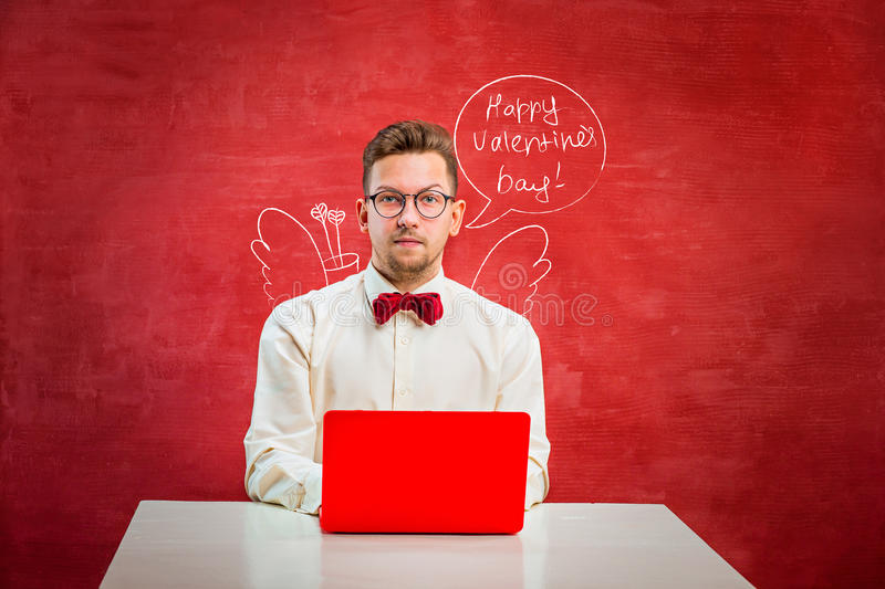 Young funny man with laptop at St. Valentine`s Day stock images