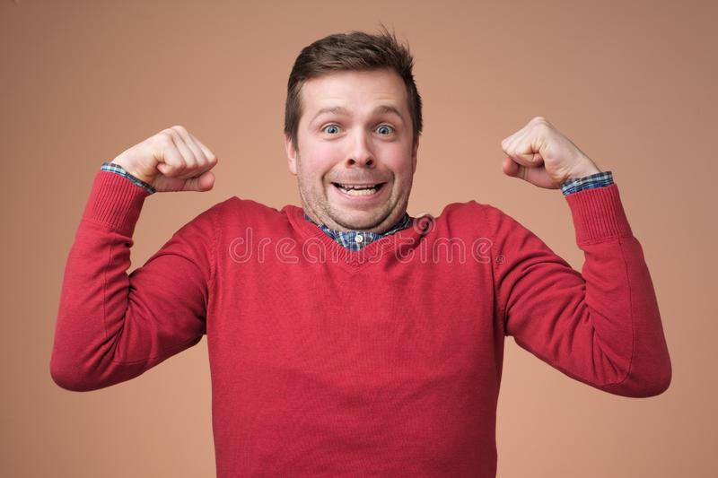 Young funny man in red sweater, shows biceps over white background. stock image