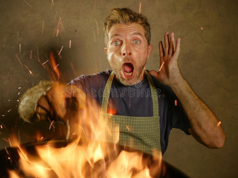 Young funny and messy home cook man with apron in shock holding pan in fire burning the food in kitchen disaster and domestic cook. Young funny and messy home royalty free stock photo
