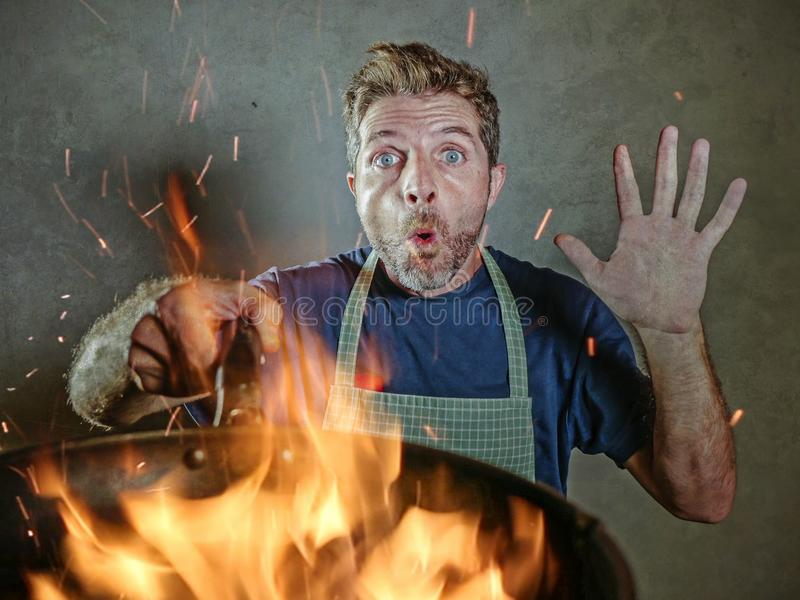 Young funny and messy home cook man with apron in shock holding pan in fire burning the food in kitchen disaster and domestic cook. Young funny and messy home royalty free stock images