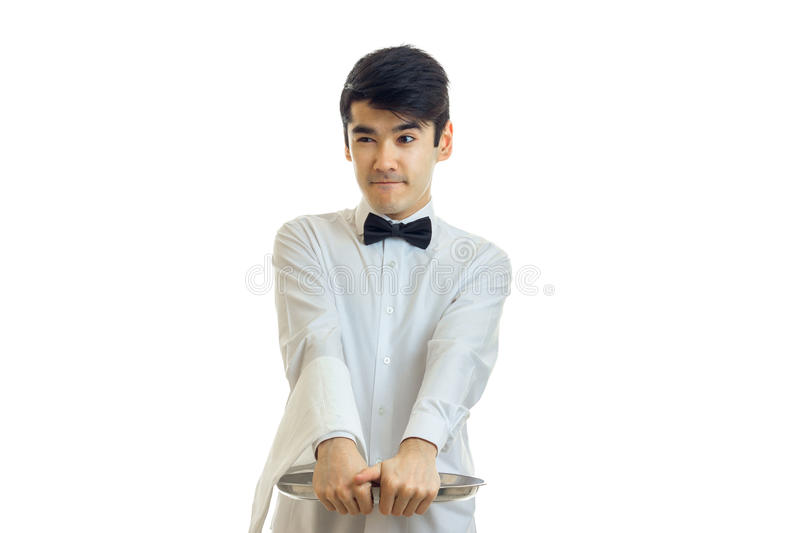 Young funny waiter in a white shirt holding before an empty tray stock photo