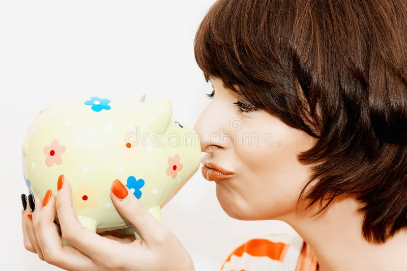 Young funny woman with decorative piggy bank royalty free stock photo