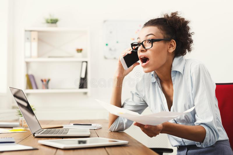 Business talk, furious woman talking on phone at office. Young furious african-american woman talking on phone at modern office copy space. Business consulting royalty free stock photo
