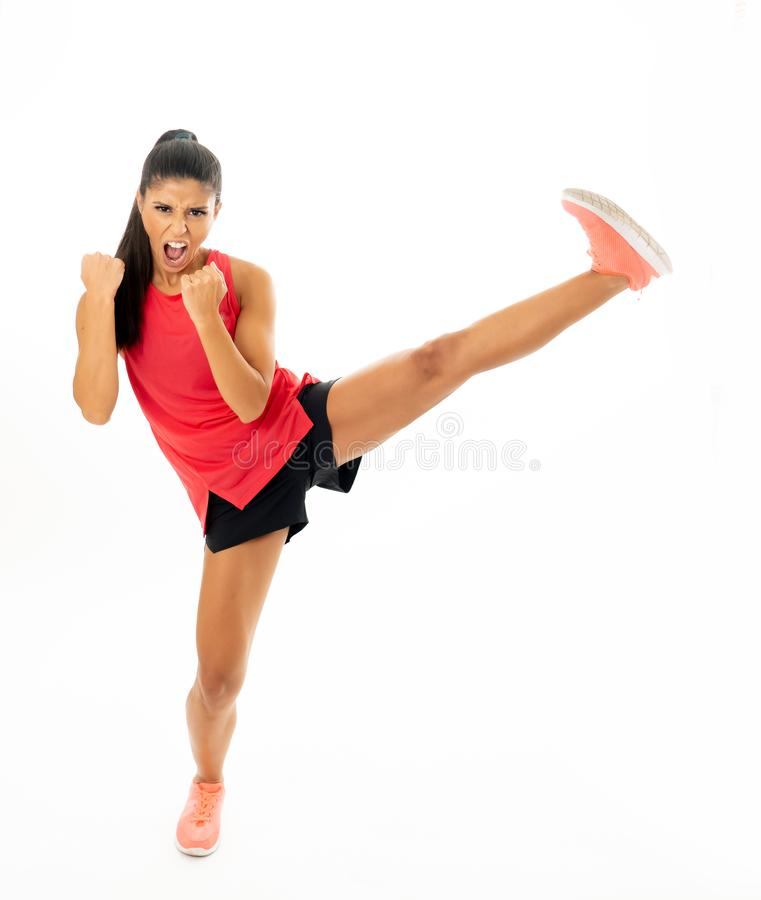 Full length shot of fit woman athlete performing a high kick martial Karate style. Young and furious latin woman in fight and kick boxing training workout stock photos