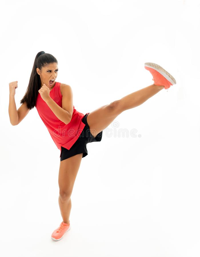 Full length shot of fit woman athlete performing a high kick martial Karate style. Young and furious latin woman in fight and kick boxing training workout royalty free stock photography
