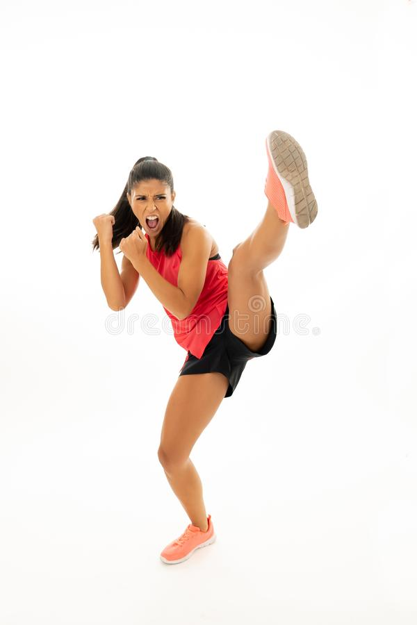 Full length shot of fit woman athlete performing a high kick martial Karate style. Young and furious latin woman in fight and kick boxing training workout stock photography