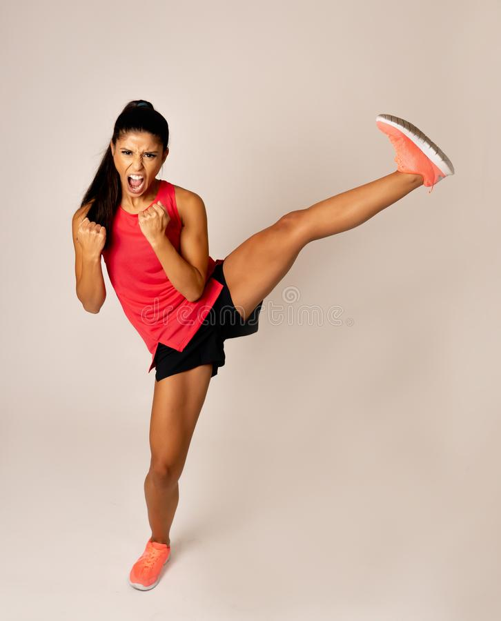 Full length shot of fit woman athlete performing a high kick martial Karate style. Young and furious latin woman in fight and kick boxing training workout stock image