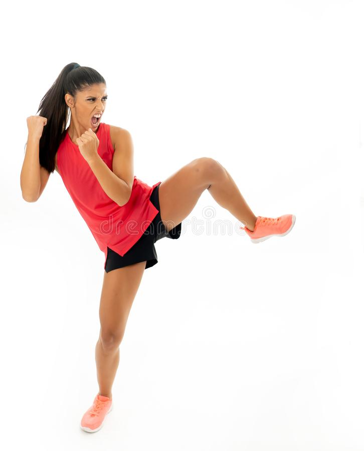 Full length shot of fit woman athlete performing a high kick martial Karate style. Young and furious latin woman in fight and kick boxing training workout stock images