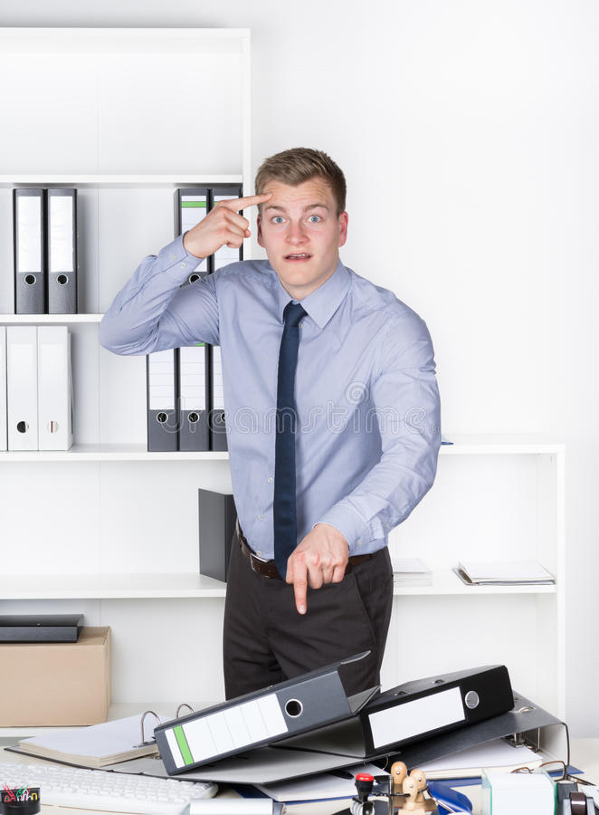 Young furious man is pointing to his head with finger. Young furious businessman is standing in front of many files on his desk in the office. He is pointing stock photos
