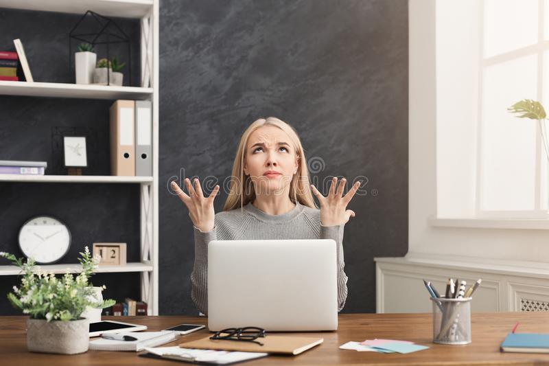 Furious woman working on laptop at office. Young furious woman working on laptop, sitting with raised hands and rolled eyes asking for patience at modern office stock photography