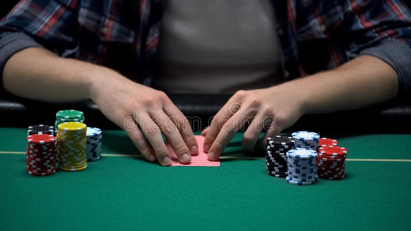 Young gambler ready to check his cards at casino poker game table, chance to win royalty free stock photo