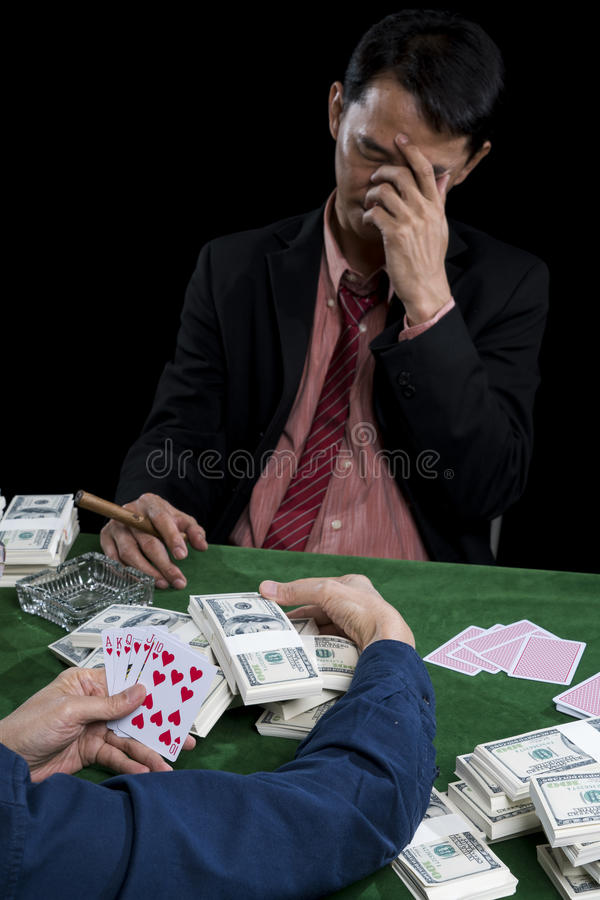 The young gambler use hand off the face and stressed when contender gathered a pile of bet royalty free stock photo