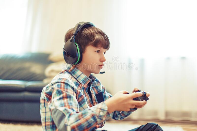 Young gamer kid concentrating while playing stock image