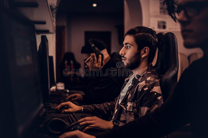 A young Indian gamer plays in a multiplayer video game on pc in a gaming club, enjoying spending time with her friends. A young gamer plays in a multiplayer royalty free stock photo