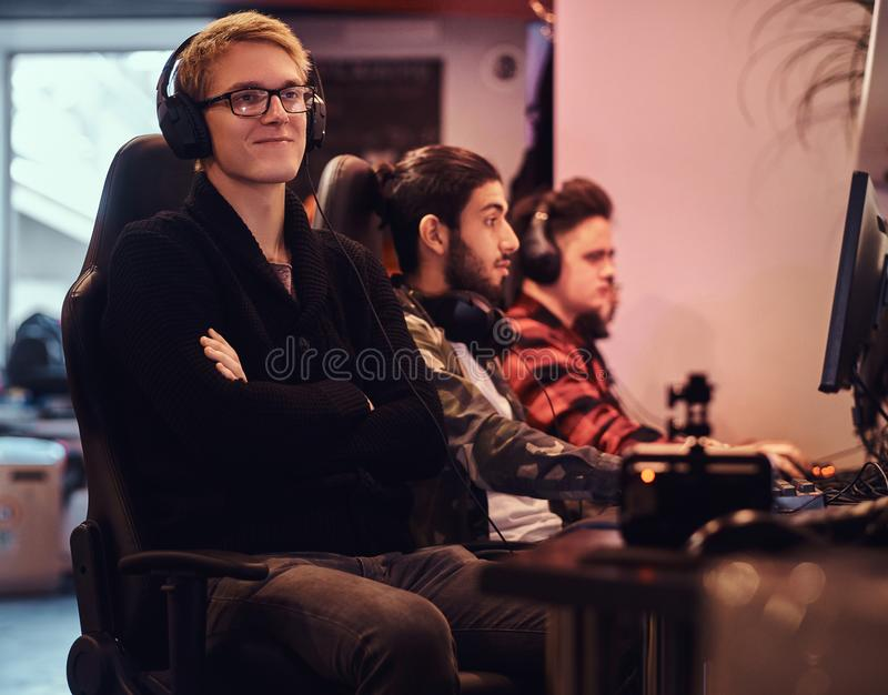 A smiling gamer wearing a sweater and glasses with his arms crossed sitting on a gamer chair in a gaming club or. Young gamer wearing a sweater and glasses with stock photography