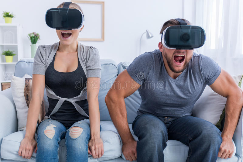 Young gamers wearing VR goggles. Shot of a young gamers sitting on a sofa and wearing VR goggles royalty free stock photo