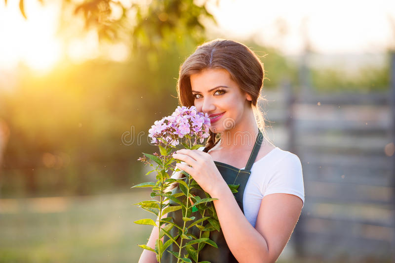 Young gardener in her garden smelling flowers, sunny nature stock photography