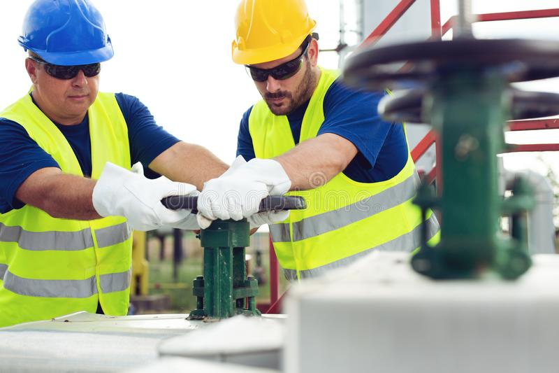 Gas Production Operators. Young Gas Production Operators on the oil and gas plant royalty free stock image