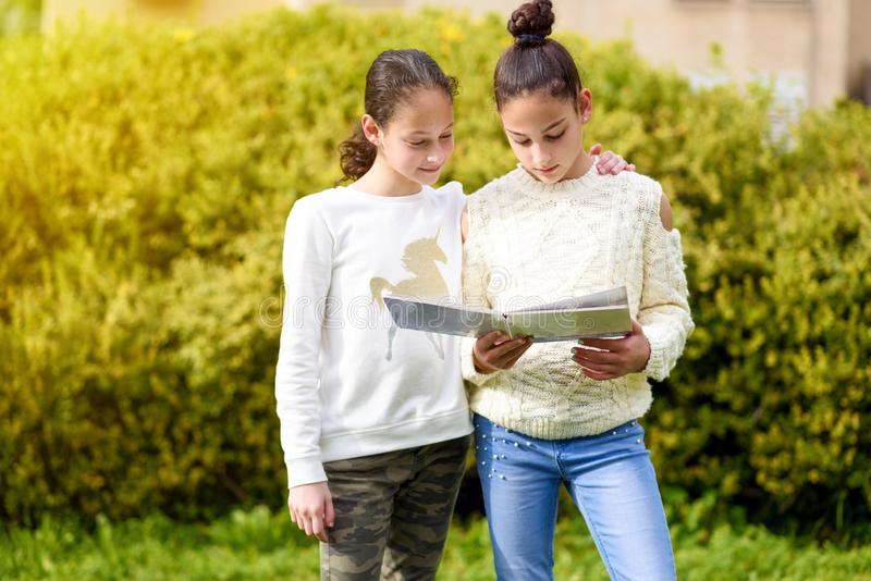 Young Generation.Two Happy Girls Reading A Book Together At Sunny Day. stock images