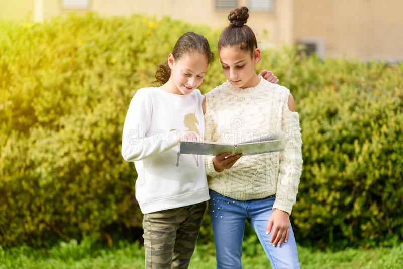 Young Generation.Two Happy Girls Reading A Book Together At Sunny Day. royalty free stock photo