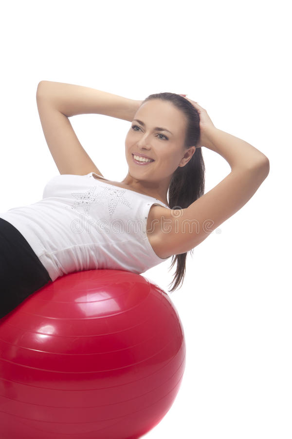 Young girl accomplishing back muscles training. Young caucasian girl exercising with fitball having positive facial expression, isolated stock photography