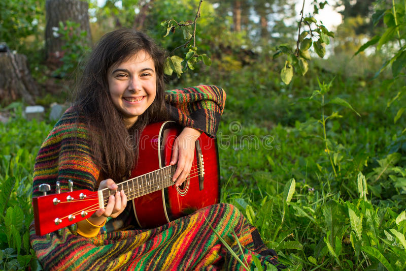 Young girl with an acoustic guitar sitting in the grass. Fun. stock image