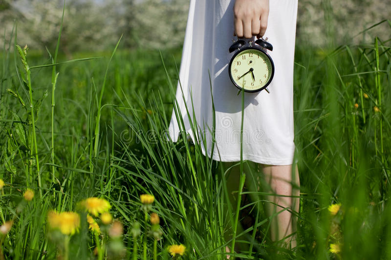Young girl with an alarm clock in her hands stock image