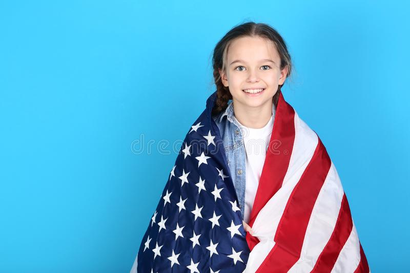 Girl with American flag. Young girl with American flag on blue background royalty free stock image