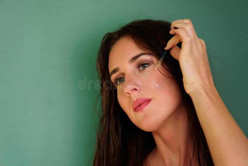 Young girl applying eye serum over green background with copy space. Skin care, pure beauty, body treatment, cosmetics concept.  stock photo