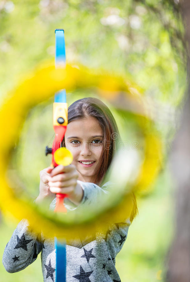 Young girl archer with bow aiming through flower wreath royalty free stock images