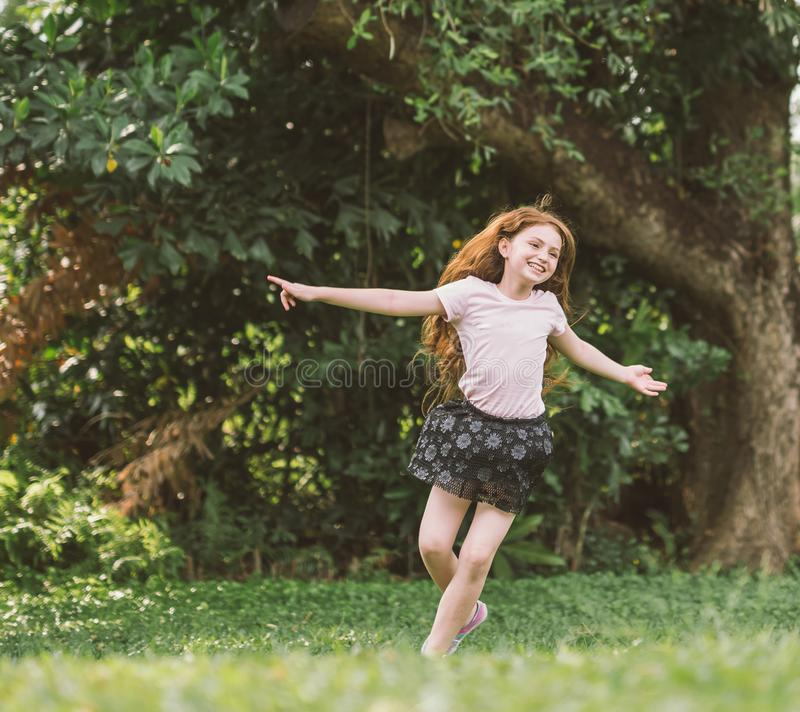 Young girl with arms open enjoying her freedom at the park so happy relax dance royalty free stock image