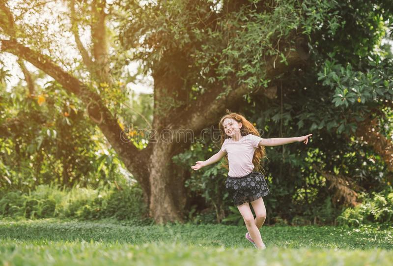 Young girl with arms open enjoying her freedom at the park so happy relax dance. royalty free stock photos