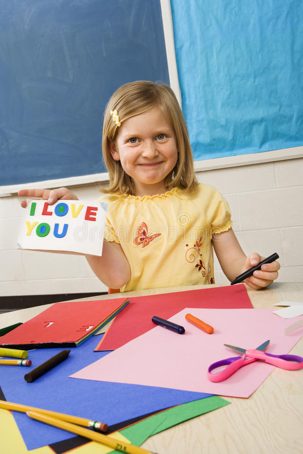 Young Girl in Art Class. Young girl showing card made in art class that says I love you stock photos