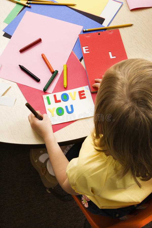 Young Girl in Art Class. Young girl making card in art class that says I love you. Vertical shot royalty free stock photography