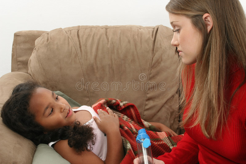 Young girl with asthma. A view of a young girl suffering from asthma, being cared for by a teenage girl royalty free stock photography