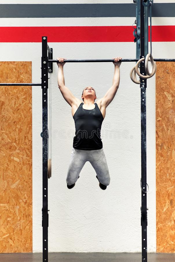 Young girl athlete doing pull-ups on a bar. Young fit strong muscular girl athlete doing pull-ups on a bar during her workout in a full frontal view inside a royalty free stock photo