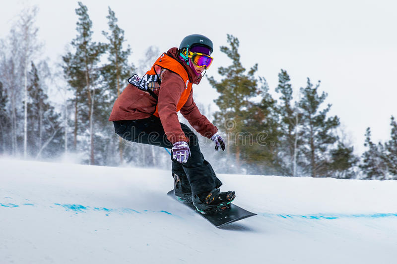 Young girl athlete snowboarder coming down mountain royalty free stock images
