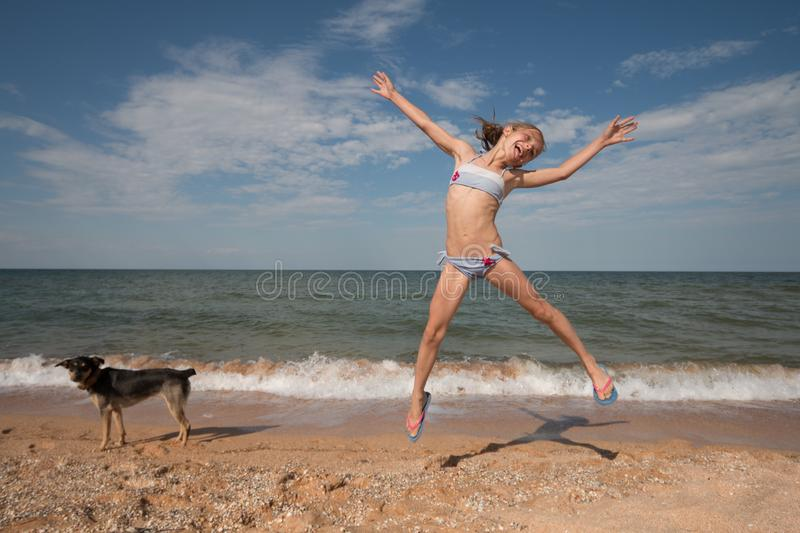 Young girl athlete in a swimsuit on the sea jumping on the beach royalty free stock photo