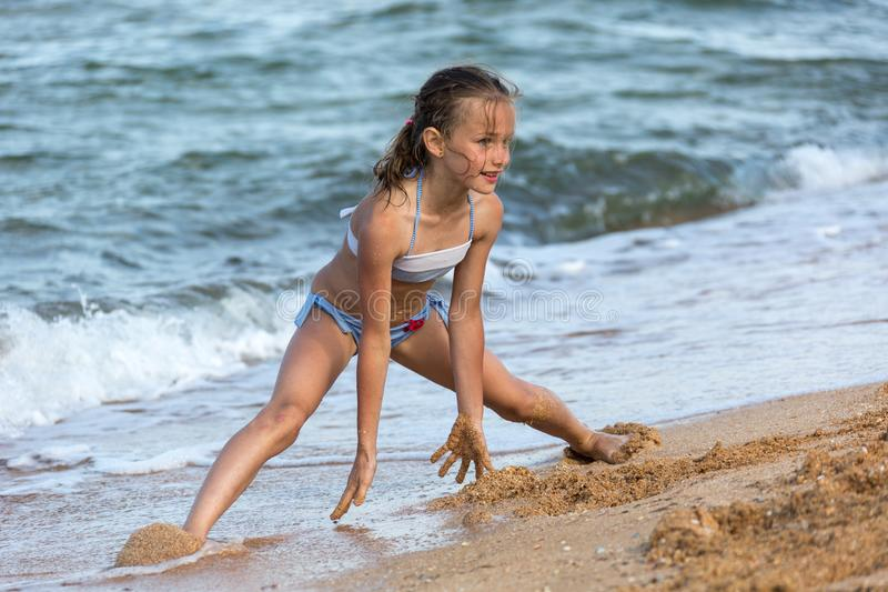 young girl athlete in a swimsuit at sea playing on the beach royalty free stock images