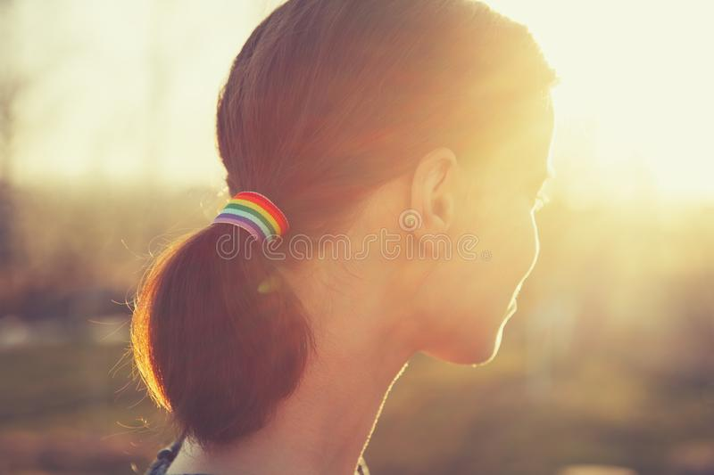 Young girl from back side with LGBT rainbow ribbon in her hair in ponytail royalty free stock image
