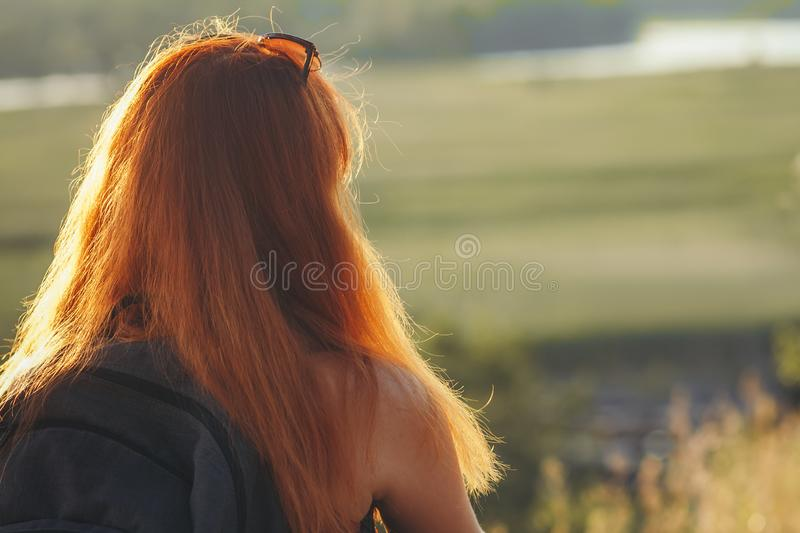 Silhouette of a red-haired girl standing near a tree and playing a wind instrument at sunset, young woman with a saxophone in royalty free stock photography