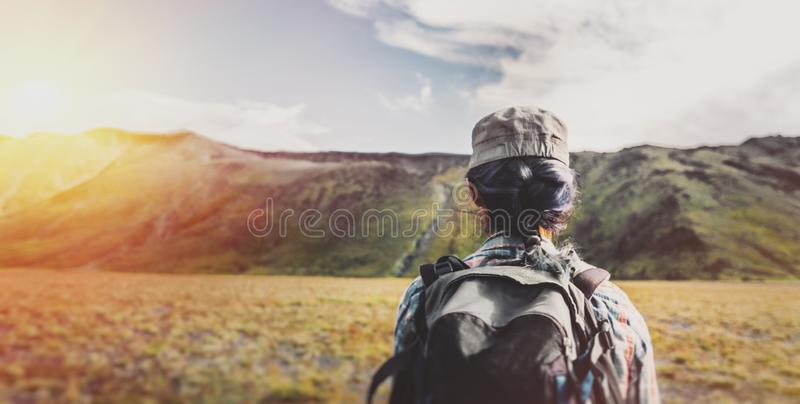 Young girl with backpack hiking in the mountains in the summer. Young Traveler Girl With Backpack Is Engaged In Hiking In Mountains, Rear View. Tourism Adventure royalty free stock photos
