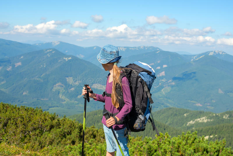 Young girl with backpack in mountains royalty free stock photo