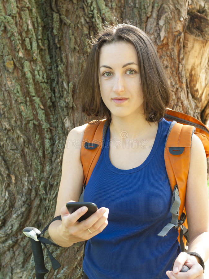 A young girl with a backpack use the phone. The girl with the backpack uses the phone during a camping trip royalty free stock image