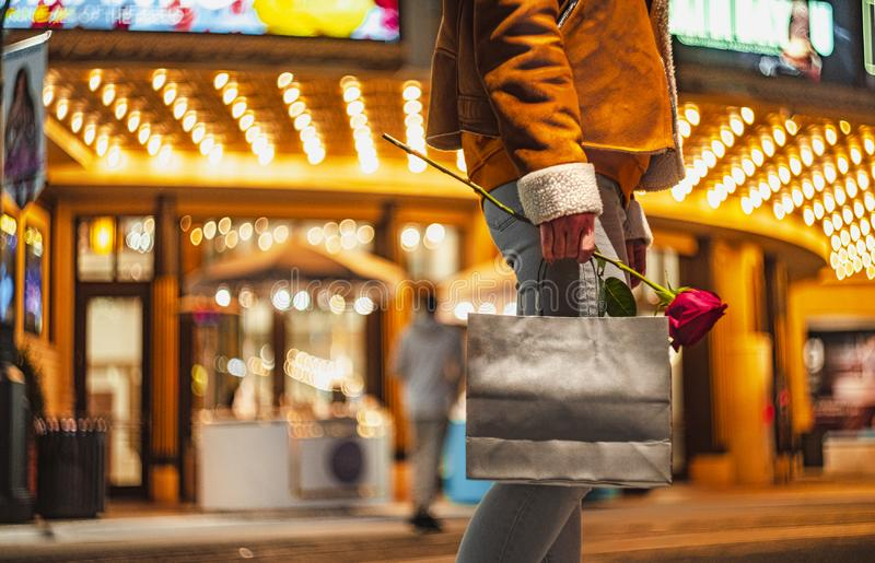 Young girl with a bag and a rose. At the cinema stock photos